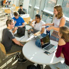 A group of students sitting around a round table, listening to a standing student.