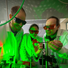 Faculty guiding students in a science lab.