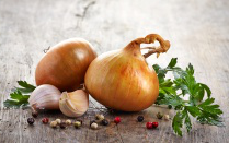 Onions and garlic on a wooden board.
