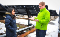 Discussing sustainability in front of solar panels.