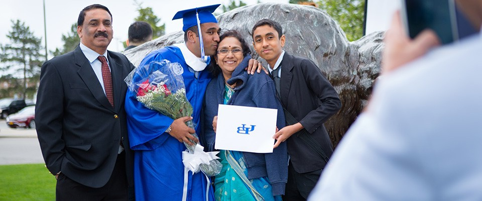 Student at graduation taking a photo with his family.