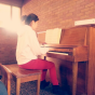 Esther on piano with sunlight.