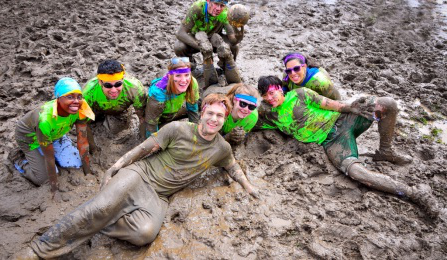 Students playing in a mud pit.