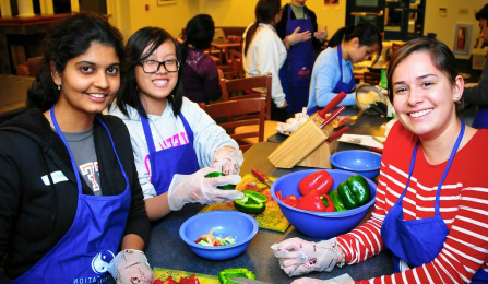 Students in aprons preparing food at a cultural cooking event.