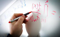 A math formula is pictured on a whiteboard.