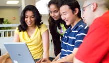 International students looking at a laptop.