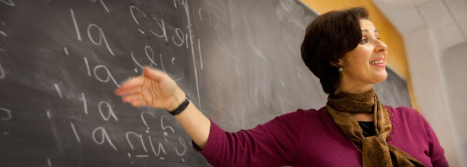 A woman with short hair stands gesturing toward a chalkboard, speaking.