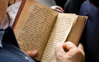 Photo of hands holding a prayer book with Jewish text.
