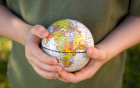Photo of hands holding a small globe.