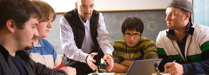 A professor and diverse group of students huddle around a laptop in a classroom setting.
