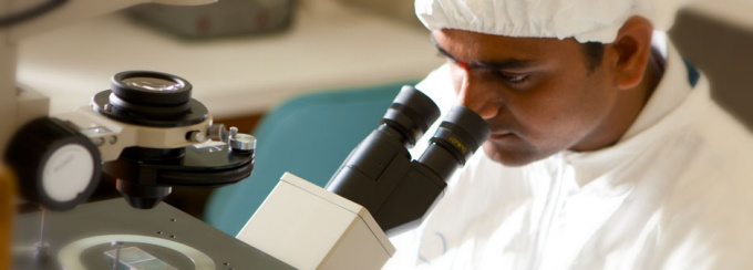 A researcher at a microscope in the clean room.