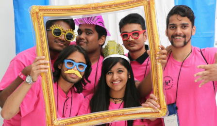 Students posing in a photo booth with props.